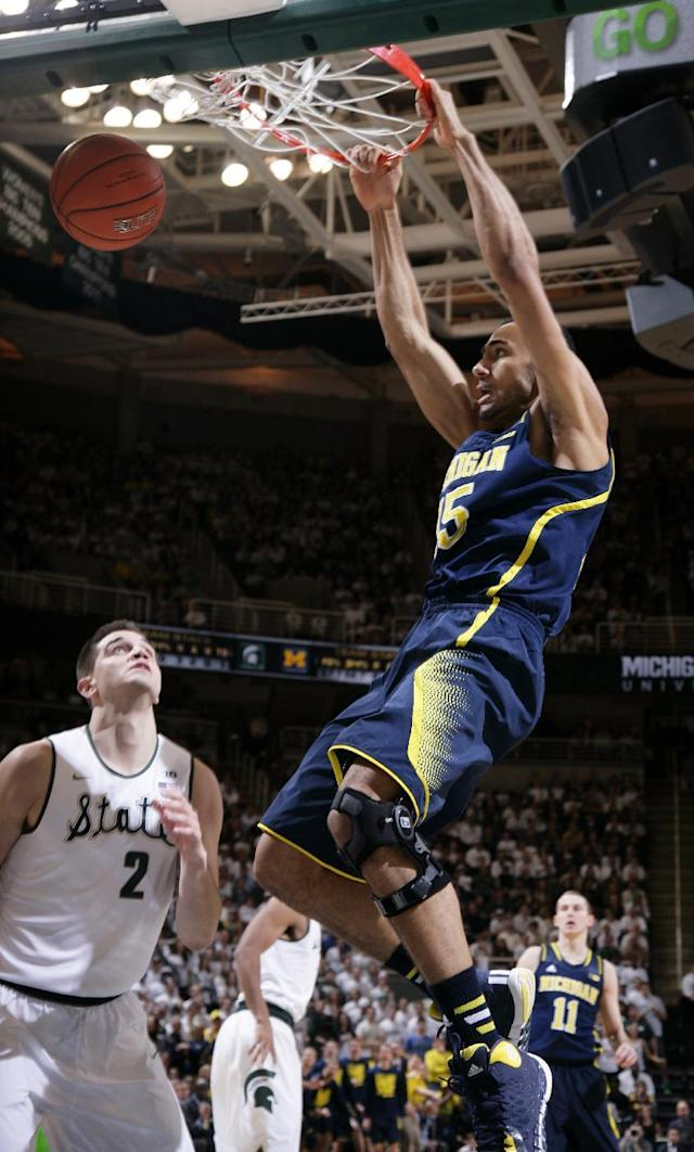 Michigan's Jon Horford, right, dunks against Michigan State's Alex Gauna (2) during the first half of an NCAA college basketball game, Saturday, Jan. 25, 2014, in East Lansing, Mich. (AP Photo/Al Goldis)