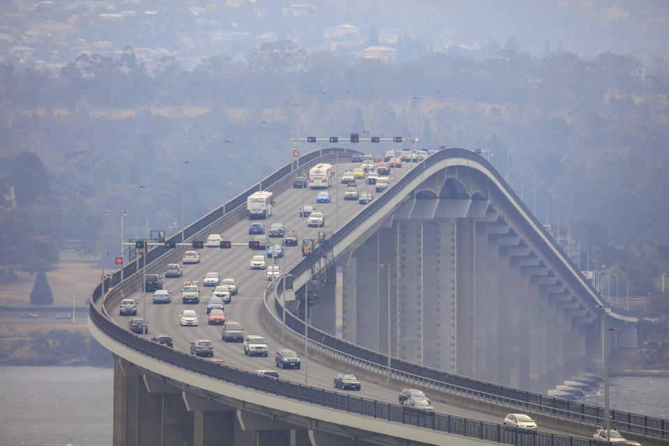 Smoke from multiple uncontrolled wildfires is seen at the Tasman Bridge in Hobart. Source: AAP