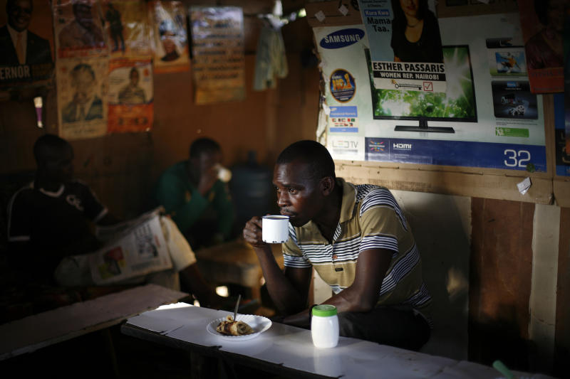 """A man drinks coffee in the Kibera slum of Nairobi, Kenya, Thursday, March 7, 2013. Kenyans on Monday held their first presidential vote since the nation's disputed election in 2007 spawned violence that killed more than 1,000 people. The coalition of Kenya's prime minister Raila Odinga says the vote tallying process now under way to determine the winner of the country's presidential election """"lacks integrity"""", should be stopped, and the counting process should be restarted using primary documents from polling stations. (AP Photo/Jerome Delay)"""