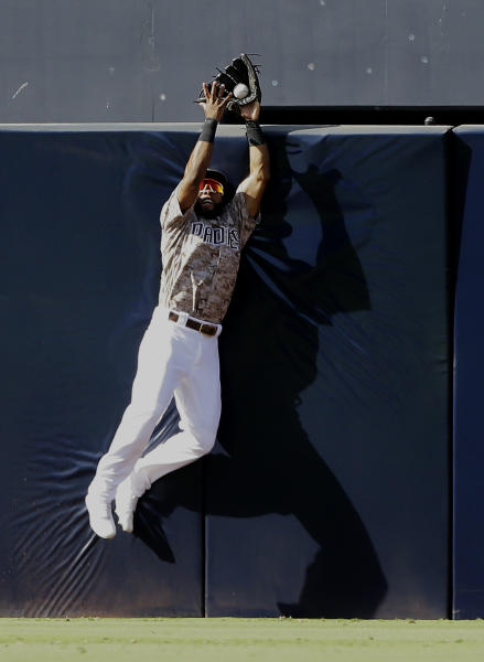 San Diego Padres center fielder Manuel Margot leaps to catch a ball at the fence hit by Arizona Diamondbacks Christian Walker during the seventh inning of a baseball game in San Diego, Sunday, Sept. 22, 2019. (AP Photo/Alex Gallardo)
