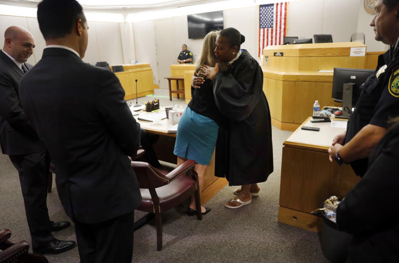 Former Dallas Police Officer Amber Guyger gives State District Judge Tammy Kemp a hug after the judge had given her a Bible and before Guyger left for jail, Wednesday, Oct. 2, 2019, in Dallas. Guyger, who said she mistook neighbor Botham Jean's apartment for her own and fatally shot him in his living room, was sentenced to a decade in prison. (Tom Fox/The Dallas Morning News via AP, Pool)