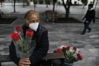 """Wearing a mask to curb the spread of the new coronavirus, Martha Gonzalez Reyes, 76, sells roses outside Metro Hidalgo in central Mexico City, Monday, Aug. 10, 2020. After four months at home, Gonzalez returned to selling on August 1, but said business hasn't fully rebounded. """"People have less money to spend, and they don't want to go out and get infected,"""" said Gonzalez. (AP Photo/Rebecca Blackwell)"""