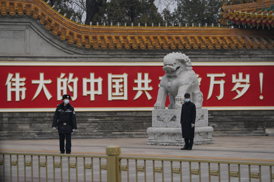 Chinese security personnel guard an entrance to the Zhongnanhai leadership compound near the words