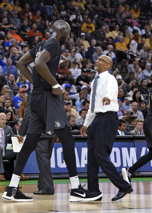 Central Florida coach Johnny Dawkins, right, speaks to Tako Fall during a first-round game in the NCAA mens college basketball tournament Friday, March 22, 2019, in Columbia, S.C.(AP Photo/Richard Shiro)