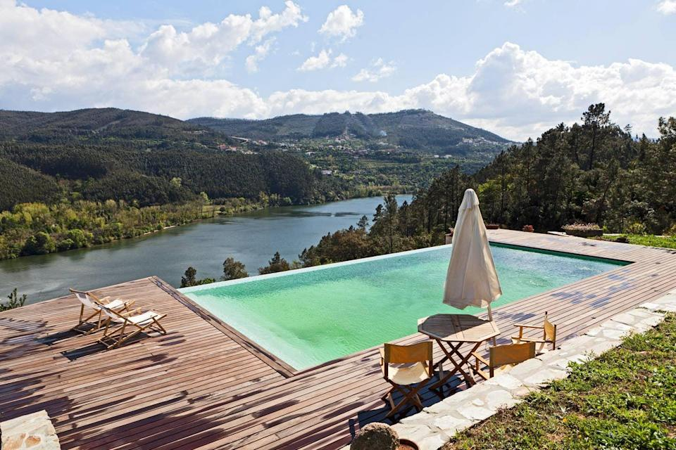 "Any dreams you've had of owning a European country home can be (temporarily) met with a stay at this rustic, cozy home. The backyard is breathtaking, with an infinity pool jetting out over the <a href=""https://www.cntraveler.com/story/why-you-should-take-a-douro-river-cruise?mbid=synd_yahoo_rss"" rel=""nofollow noopener"" target=""_blank"" data-ylk=""slk:Douro River"" class=""link rapid-noclick-resp"">Douro River</a> and a multi-layered deck. Dining tables extend out from the living and indoor dining room, and the kitchen looks straight out of a movie set, with pots and pans hanging from the stone wall and all sorts of family heirlooms, from tea kettles to mismatched dishware and wicker baskets. With provisions like fruit, bread, cheese, and wine often left out for guests, it feels like a stay at your family's (very beautifully located) cabin. $387, Airbnb (starting price). <a href=""https://www.airbnb.com/rooms/403641"" rel=""nofollow noopener"" target=""_blank"" data-ylk=""slk:Get it now!"" class=""link rapid-noclick-resp"">Get it now!</a>"