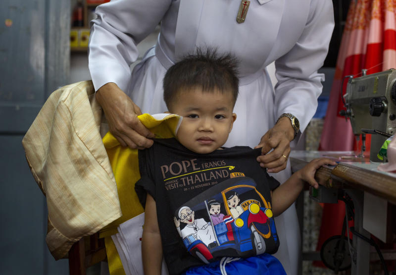 In this Friday, Nov. 8, 2019 photo, a boy wears a T-shirt marking Pope Francis' visit to Thailand at a Catholic preparatory school in Bangkok, Thailand. Pope Francis will arrive in Thailand on Nov. 20, before heading off to Japan three days later, where a new set of tailor-made robes will await him. (AP Photo/Gemunu Amarasinghe)