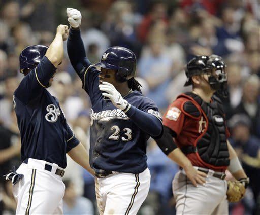 Milwaukee Brewers' Rickie Weeks (23) is congratulated by George Kottaras near Houston Astros catcher Chris Snyder after Weeks hit a three-run home run during the sixth inning of a baseball game Tuesday, April 24, 2012, in Milwaukee. (AP Photo/Morry Gash)