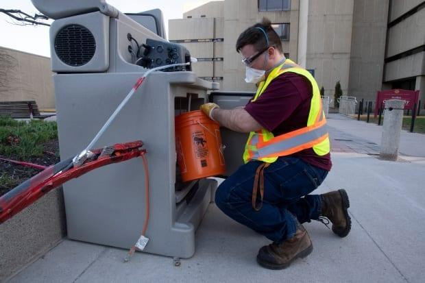 Student Patrick D'Aoust places a wastewater collection container inside a pump station on the University of Ottawa campus on Thursday, April 8, 2021.