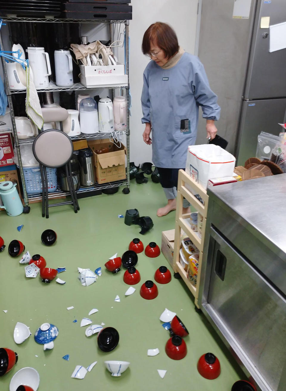A landlady of a Japanese style hotel stands near damaged bowls following an earthquake in Minamisoma, Fukushima prefecture, northeastern Japan Saturday, Feb. 13, 2021. The Japan Meteorological Agency says a strong earthquake has hit off the coast of northeastern Japan, shaking Fukushima, Miyagi and other areas. (Tomomi Miura/Kyodo News via AP)