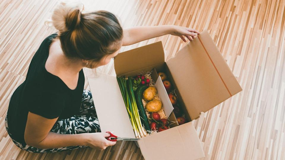 woman opening a vegetable delivery box at home, online ordering.