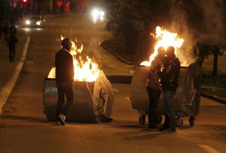 Opposition protesters stand near burning dumpsters as they gather in front of the parliament building in Pristina