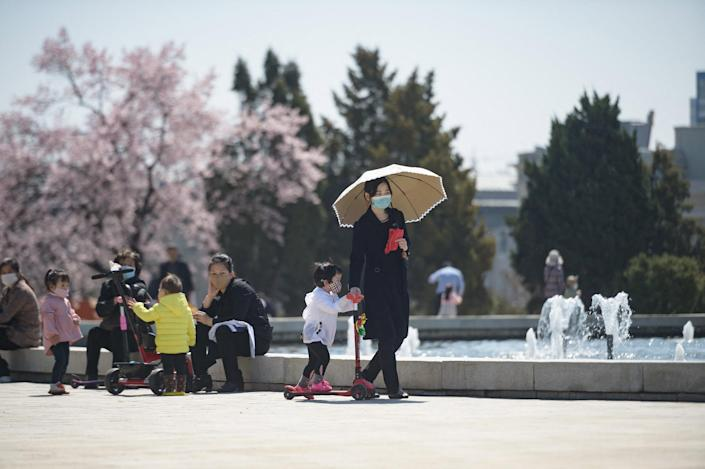 Image: A woman and child walk before a fountain in a park next to the Grand People's Study House in Pyongyang, North Korea. (Kim Won Jin / AFP via Getty Images)