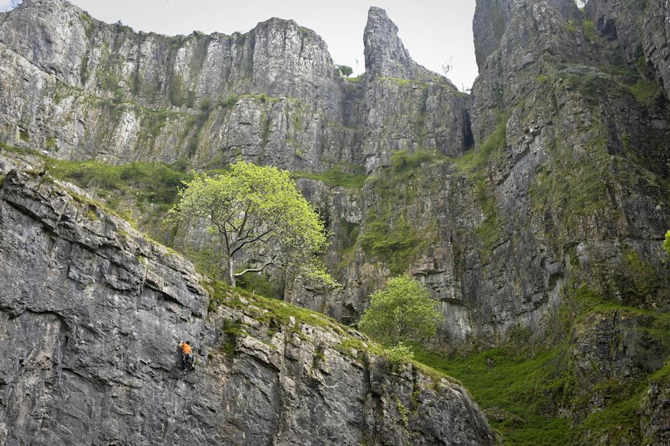A rock climber dressed in orange reaches for a hand-hold as he attempts the climb at the 'Crag AttaK' event taking place in Cheddar Gorge, Somerset, where rock climbers from all over the word are converging in Britain's Biggest Gorge to take part in the Cheddar Gorge Challenges.