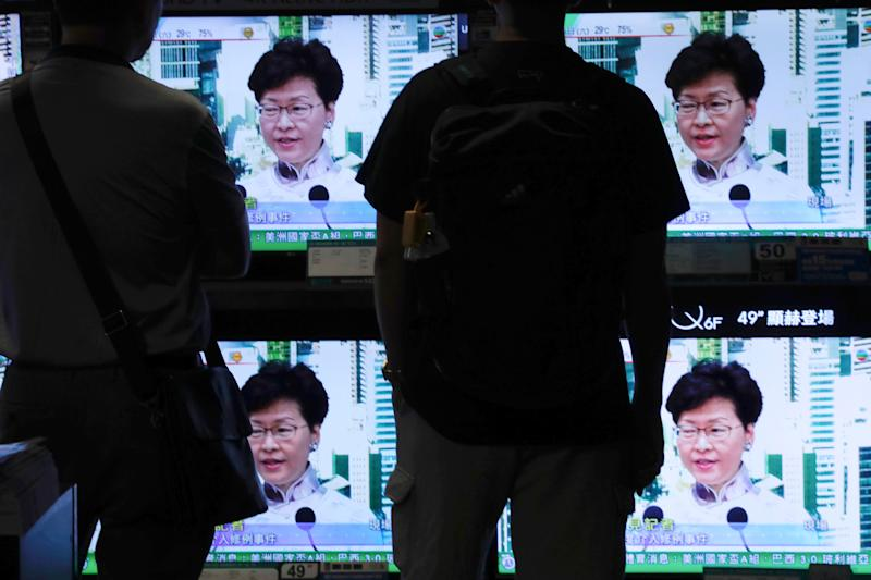Residents watch a broadcast of Chief Executive Carrie Lam speaking at a press conference held in Hong Kong on Saturday, June 15, 2019. Lam said she will suspend a proposed extradition bill indefinitely in response to widespread public unhappiness over the measure, which would enable authorities to send some suspects to stand trial in mainland courts.