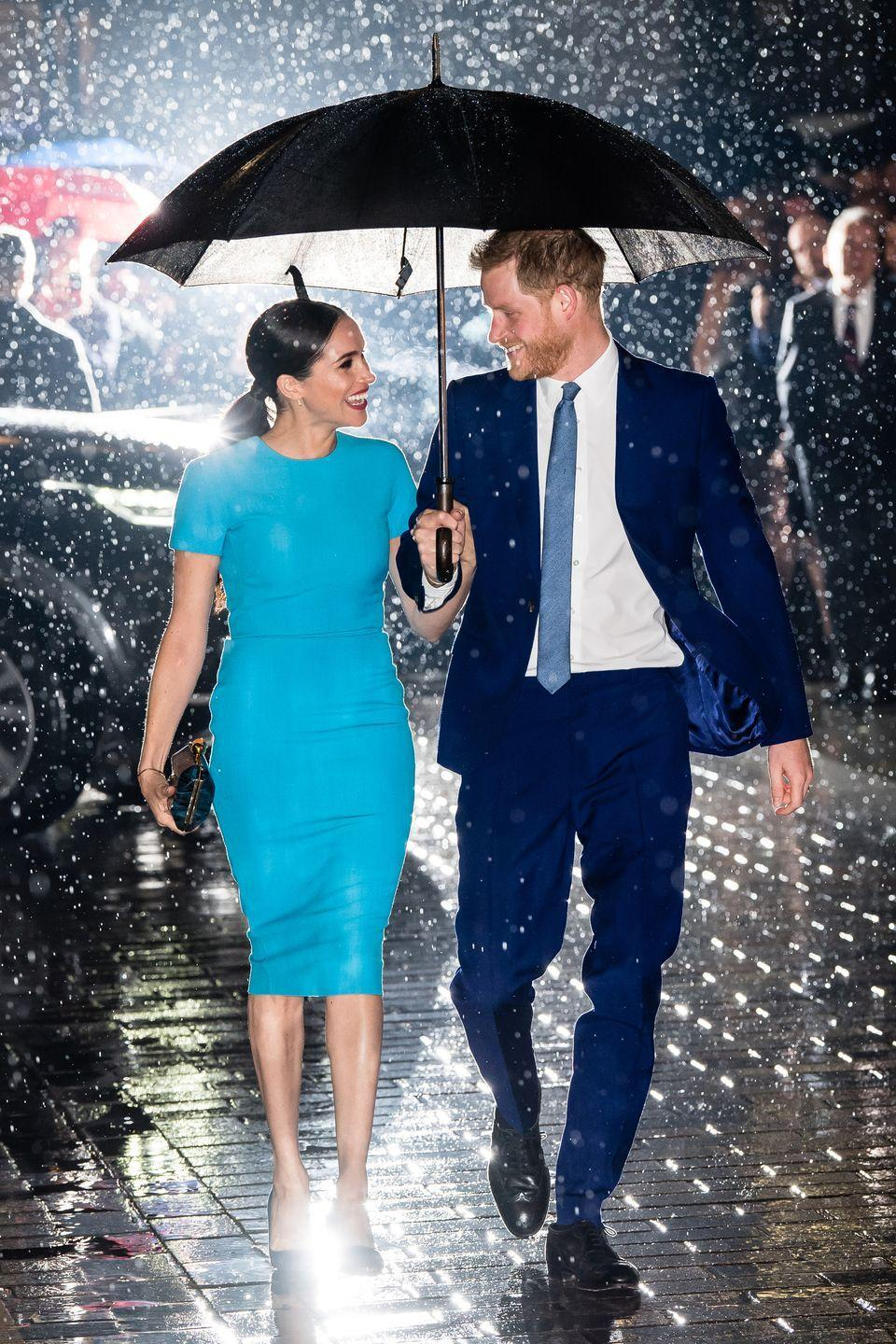 <p>The Duke and Duchess of Sussex smile at each other under an umbrella while walking to the Endeavor Fund Awards.</p>
