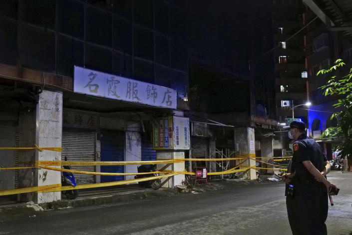 A security person stands across the street from a burnt building in Kaohsiung in southern Taiwan, Thursday, Oct. 14, 2021. Officials say at least 46 people were killed and over 40 injured after a fire broke out in a decades-old mixed commercial and residential building in the Taiwanese port city of Kaohsiunging. Neighborhood residents say the 13-story building was home to many poor, elderly and disabled people and it wasn't clear how many of the 120 units were occupied. (AP Photo/Huizhong Wu)