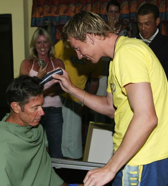 ST. GEORGE'S, GRENADA - MAY 31:  Coach John Buchanan of Australia has his head shaved by Brett Lee on May 31, 2003 at the Grenada Grand Beach Resort in St George's, Grenada.  Buchanan honoured an agreement from the World Cup where he stated he would shave his head if the Australians won. (Photo by Hamish Blair/Getty Images)
