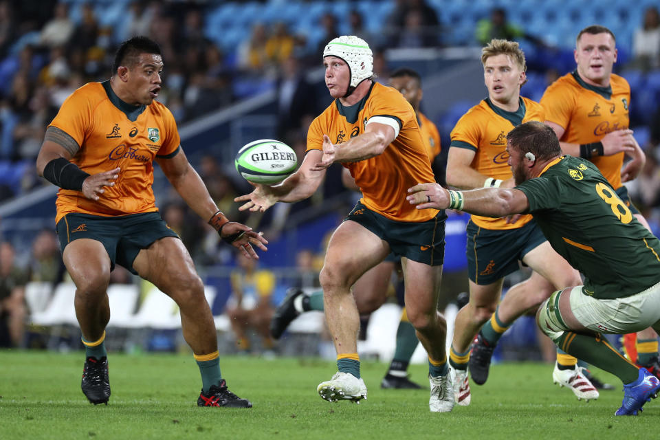 Australia's Michael Hooper, center, unloads the ball to teammate Allan Alaalatoa as South Africa's Duane Vermeulen, right, comes in to tackle during their Rugby Championship match on Sunday, Sept. 12, 2021, Gold Coast, Australia. (AP Photo/Tertius Pickard)