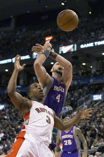 Toronto Raptors' Kyle Lowry, left, is fouled by Phoenix Suns' Marcin Gortat during the first half of an NBA basketball game Friday, Nov. 30, 2012, in Toronto. (AP Photo/The Canadian Press, Chris Young)