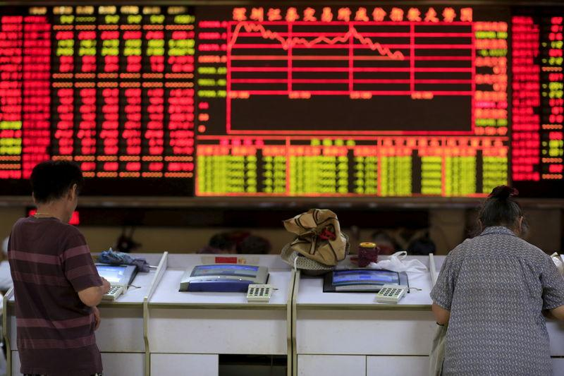 Investors look at computer screens in front of an electronic board showing stock information at a brokerage house in Shanghai, China, September 7, 2015. REUTERS/Aly Song/Files