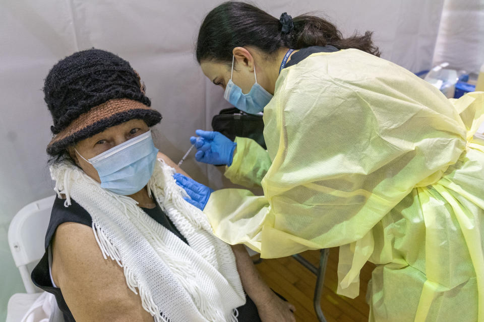 Registered Nurse Rita Alba gives a patient the first dose of the coronavirus vaccine at a pop-up COVID-19 vaccination site at the Bronx River Community Center, Sunday, Jan. 31, 2021, in the Bronx borough of New York. (AP Photo/Mary Altaffer)