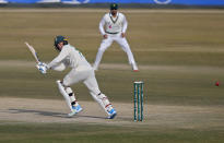South Africa's Rassie van der Dussen, front, plays shot while Pakistan's Azhar Ali watches during the fourth day of the second cricket test match between Pakistan and South Africa at the Pindi Stadium in Rawalpindi, Pakistan, Sunday, Feb. 7, 2021. (AP Photo/Anjum Naveed)