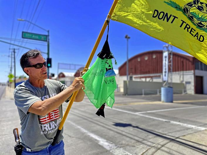 """A man in a Trump shirt with a gun on his hip waves a """"Don't Tread On Me"""" flag"""