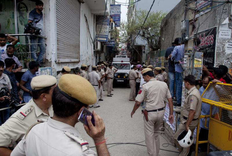 India Police next the house where 11 bodies were found in Burari village, north Delhi, India, Sunday, July 1, 2018. Ten bodies, blindfolded by cotton and pieces of cloth, were found hanging from an iron grill used as a ventilator in the home's courtyard, while the body of a 70-year-old woman was lying on the floor of the house, said a police official who spoke on condition of anonymity, in line with department policy. (AP Photo/Rishabh R. Jain)