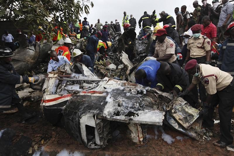 Rescue workers inspect the wreckage of a charter passenger jet which crashed soon after take off from Lagos airport, Nigeria, Thursday, Oct. 3, 2013. Officials said there were casualties but refused to confirm reports of several deaths. (AP Photo/Sunday Alamba)