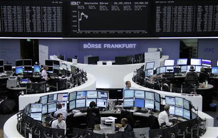 Traders are pictured at their desks in front of the DAX board at the Frankfurt stock exchange May 26, 2014. REUTERS/Remote/Stringer