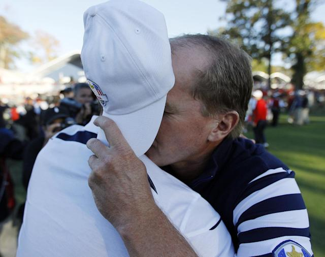 USA's Steve Stricker covers his face as he hugs Europe's Martin Kaymer after a singles match at the Ryder Cup PGA golf tournament Sunday, Sept. 30, 2012, at the Medinah Country Club in Medinah, Ill. (AP Photo/Charles Rex Arbogast)