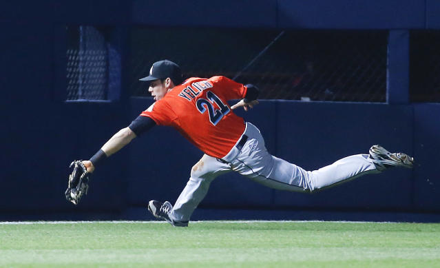 Miami Marlins left fielder Christian Yelich (21) can't reach a ball hit for double by Atlanta Braves pinch hitter Jordan Schafer in the ninth inning of a baseball game Monday, April 21, 2014 in Atlanta. Atlanta won 4-2 in the tens innings. (AP Photo/John Bazemore)