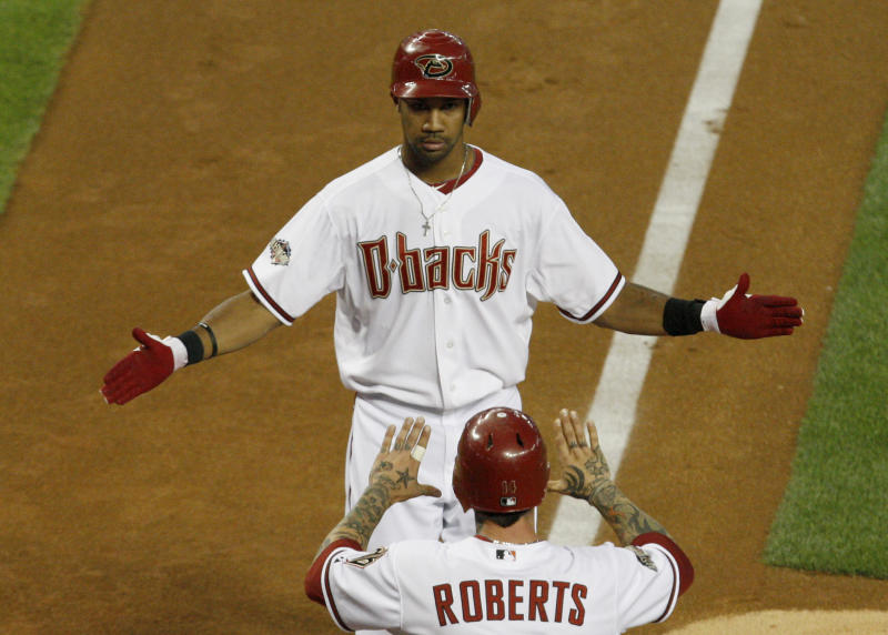 Arizona Diamondbacks' Chris Young, top, celebrates his home run against the Philadelphia Phillies with teammate Ryan Roberts during the third inning of an major league baseball game Monday, April 25, 2011, in Phoenix. (AP Photo/Ross D. Franklin)