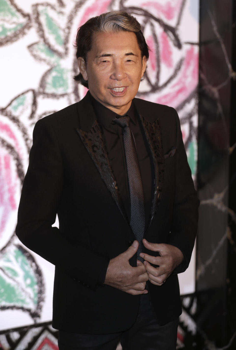 FILE - In this Saturday, March 28, 2015 file photo, Japanese fashion designer Takada Kenzo poses for photographers as he arrives at the Rose Ball in Monaco. Fashion designer Kenzo Takada dies from COVID-19 complications at age 81 near Paris, spokeswoman and reports said Sunday Oct. 4, 2020. (AP Photo/Lionel Cironneau, file)