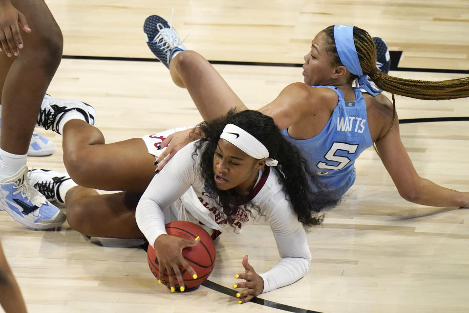 Alabama guard Jordan Lewis picks up a loose ball ahead of North Carolina guard Stephanie Watts (5) during the first half of a college basketball game in the first round of the women's NCAA tournament at the Alamodome in San Antonio, Monday, March 22, 2021. (AP Photo/Eric Gay)