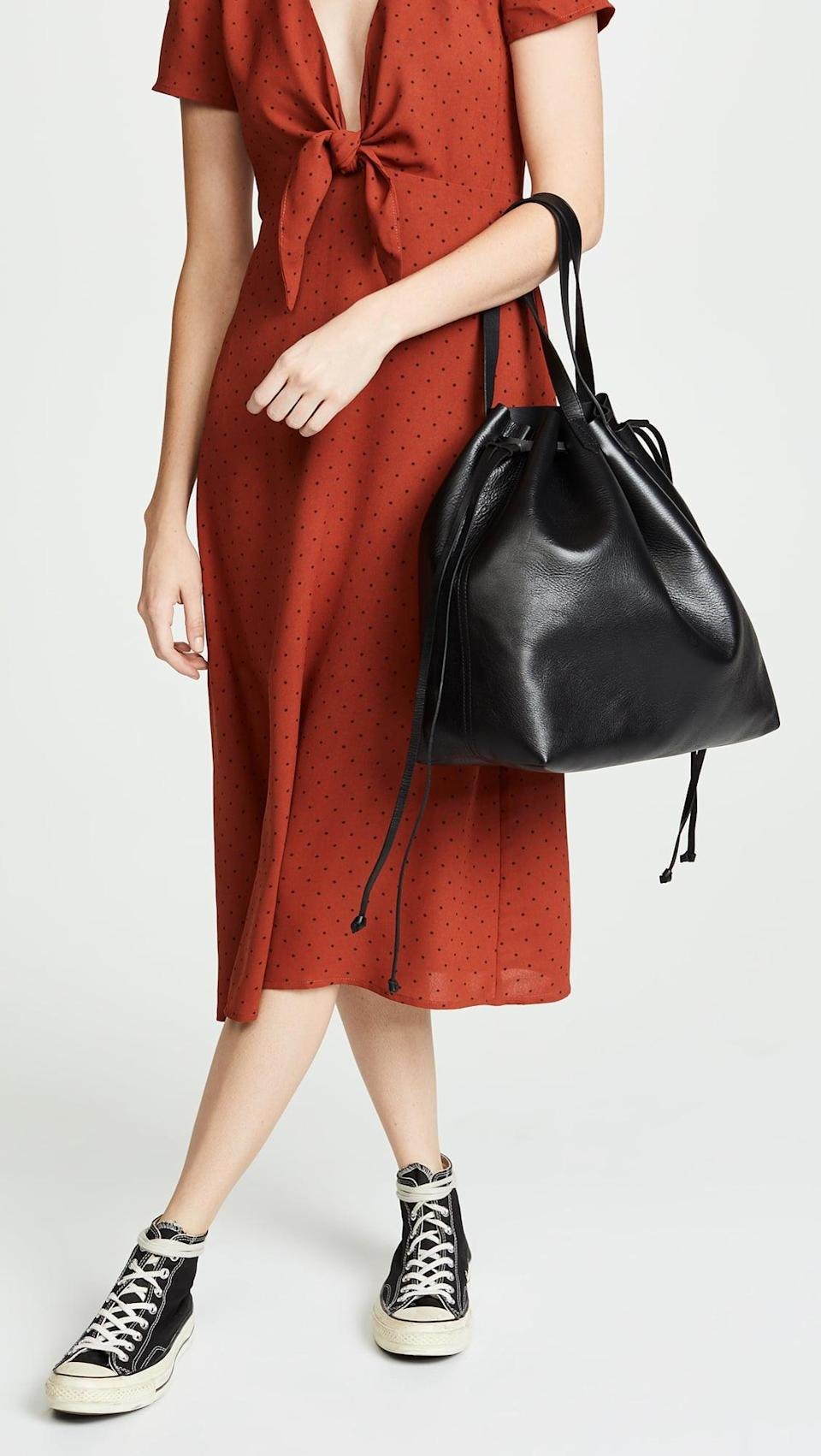 """<p>This <a href=""""https://www.popsugar.com/buy/Madewell-Drawstring-Transport-Tote-537115?p_name=Madewell%20The%20Drawstring%20Transport%20Tote&retailer=shopbop.com&pid=537115&price=178&evar1=fab%3Aus&evar9=45623846&evar98=https%3A%2F%2Fwww.popsugar.com%2Ffashion%2Fphoto-gallery%2F45623846%2Fimage%2F47066454%2FMadewell-Drawstring-Transport-Tote&list1=shopping%2Caccessories%2Cbags%2Cworkwear&prop13=mobile&pdata=1"""" class=""""link rapid-noclick-resp"""" rel=""""nofollow noopener"""" target=""""_blank"""" data-ylk=""""slk:Madewell The Drawstring Transport Tote"""">Madewell The Drawstring Transport Tote</a> ($178) is so easy to carry.</p>"""