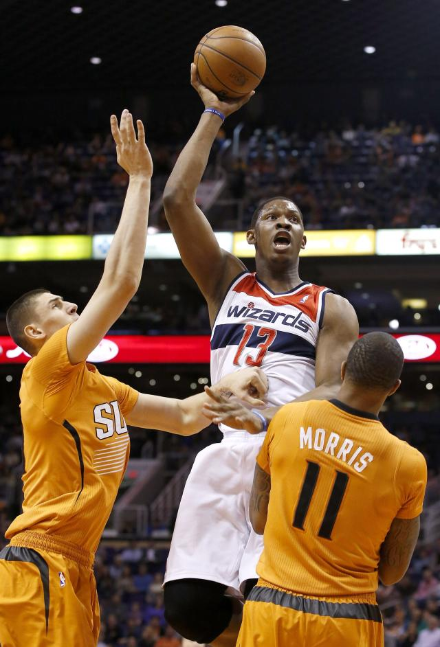 Washington Wizards' Kevin Seraphin (13), of France, gets off a shot but knocks over Phoenix Suns' Markieff Morris (11) for a charging foul as Suns' Alex Len, left, of the Ukraine, defends during the first half of an NBA basketball game, Friday, Jan. 24, 2014, in Phoenix. (AP Photo/Ross D. Franklin)