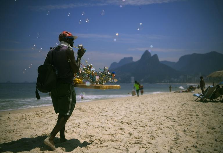 Brazilian beach vendor Marco Conceicao offers bubble toys for sale on Rio de Janeiro's Ipanema on March 19, 2020