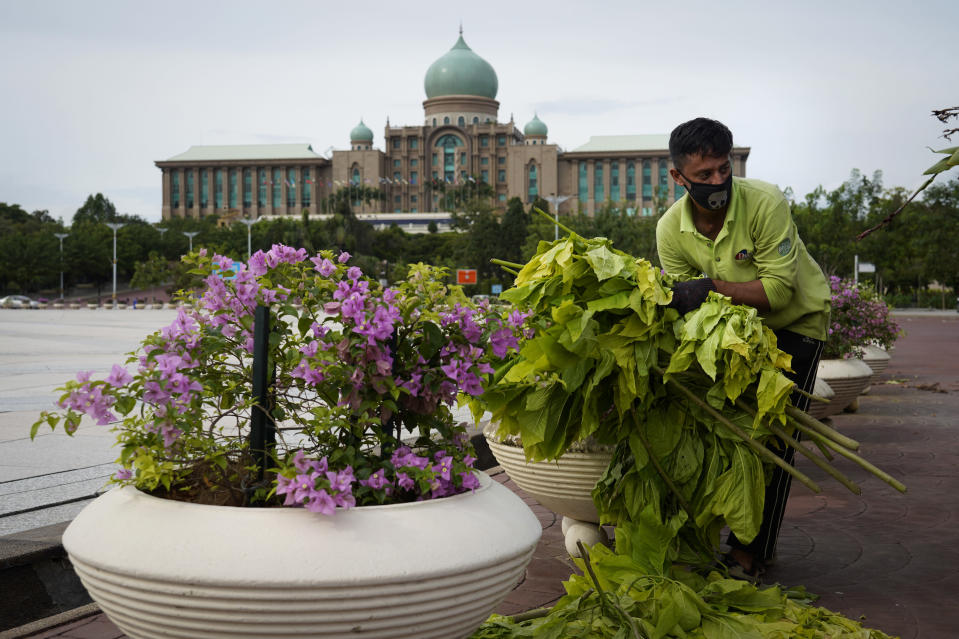 A worker cleans in front of the prime minister's office building in Putrajaya, Malaysia, Friday, Oct. 23, 2020. Malaysian opposition leader Anwar Ibrahim said Friday he was concerned about reports that Prime Minister Muhyiddin Yassi may invoke emergency laws to suspend Parliament and stymie bids to oust his government. (AP Photo/Vincent Thian)