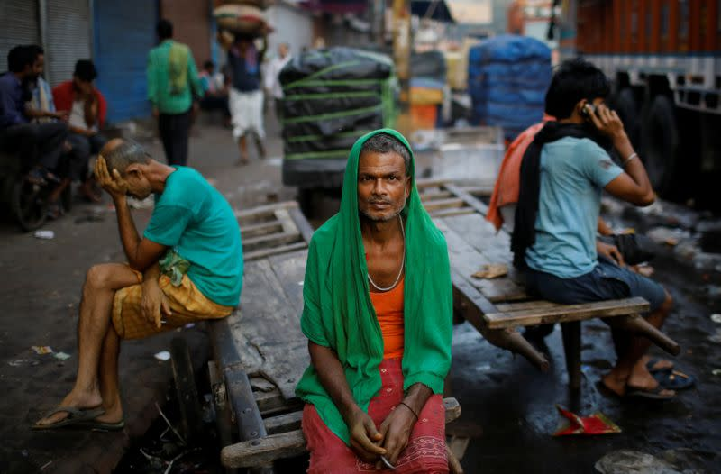 Migrant labourers sit on a handcart as they wait for work at a wholesale market in the old quarters of Delhi
