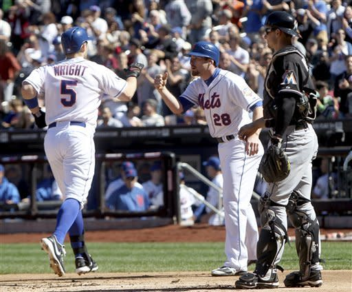 New York Mets' David Wright, left, is greeted by Daniel Murphy, center, after he hit a two-run home run while Miami Marlins catcher Rob Brantly, right, looks on during the first inning of the baseball game on Sunday, Sept. 23, 2012, at Citi Field in New York. (AP Photo/Seth Wenig)