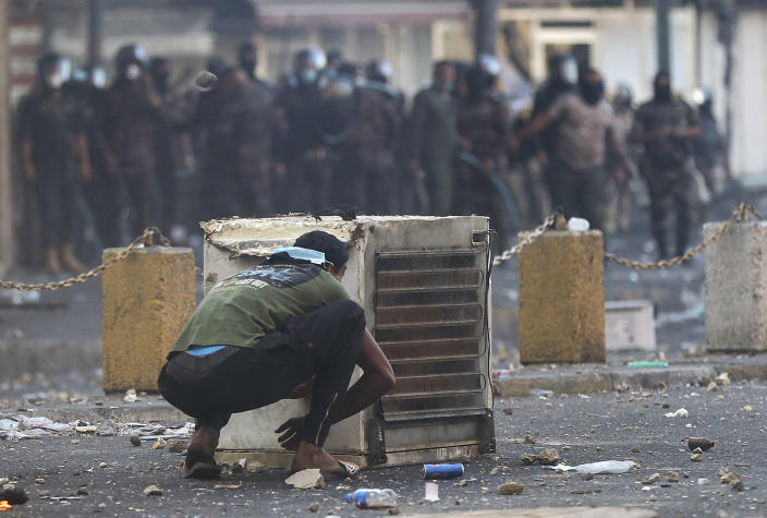 An anti-government protester crouches down during a clash with Iraqi security forces in central Baghdad, Iraq, Saturday, Nov. 9, 2019. The protests intensified Saturday afternoon as demonstrators tried to reach the three bridges, hours after being pushed back under clouds of tear gas from the Sinak bridge to the nearby Khilani square. (AP Photo/Hadi Mizban)