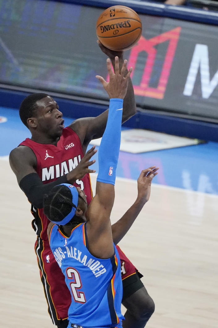 Miami Heat guard Kendrick Nunn, rear, shoots in front of Oklahoma City Thunder guard Shai Gilgeous-Alexander (2) in the second half of an NBA basketball game Monday, Feb. 22, 2021, in Oklahoma City. (AP Photo/Sue Ogrocki)
