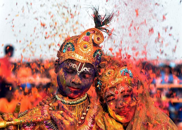 <p>Tribal Indian students from the Kalinga Institute of Social Science (KISS), dressed as Lord Krishna and Radha, are smeared with with coloured powder and petals during Holi festival celebrations in Bhubaneswar on March 1, 2018.<br> (Photo: Asit Kumar/AFP/Getty Images) </p>