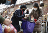 United Sherpa Association treasurer Tshering Sherpa, center, helps college students Jyoti Rajbanshi of Long Island University, left, and Lalsa Pandit of Laguardia Community College, right, pack free food in bags during the group's weekly food pantry on Friday, Jan. 8, 2021, in the Queens borough of New York. (AP Photo/Jessie Wardarski)