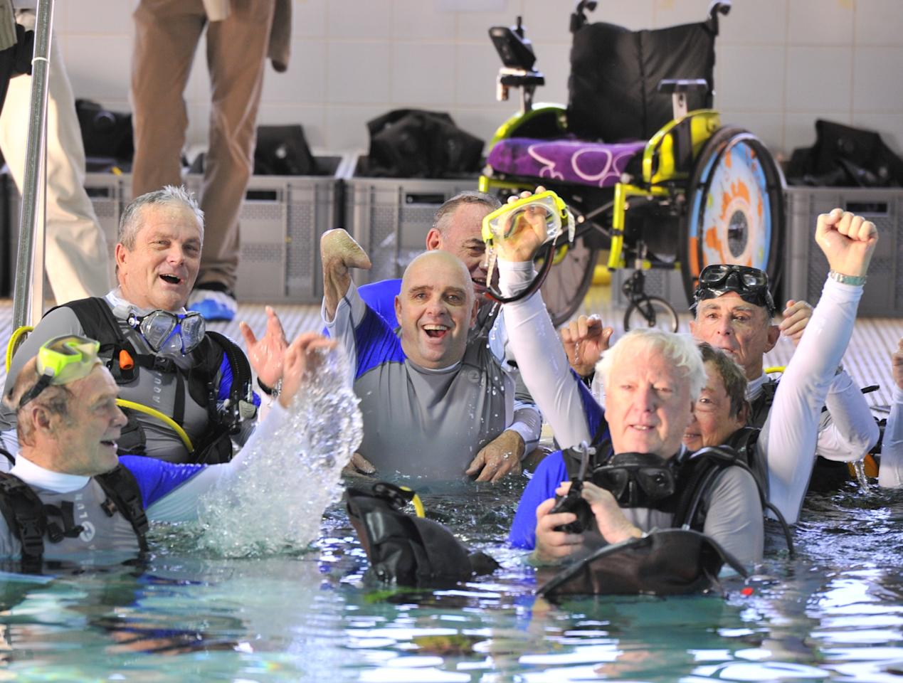French Philippe Croizon (C), 44, celebrates on January 10, 2013 with a group of 15 Belgian divers after becoming the first quadruple amputee to dive at a depth of 33 meters in the deepest swiming pool in the world in Brussels. He used flippers attached to prosthetic limbs to dive to the bottom of the pool to set a new world record for an amputee. Croizon had all four limbs amputated in 1994 after being struck by an electric shock of more than 20,000 volts as he tried to remove a TV antenna from a roof. He has swum across the English Channel and all five intercontinental channels.  AFP PHOTO  GEORGES GOBETGEORGES GOBET/AFP/Getty Images