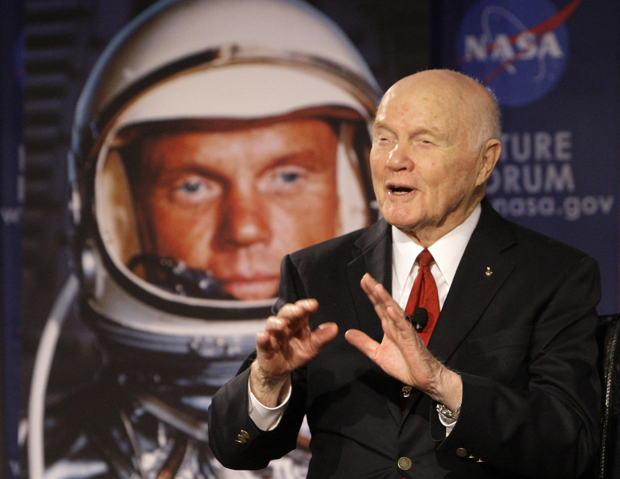 """Sen. John Glenn talks, via satellite, with the astronauts on the International Space Station, before the start of a roundtable discussion titled """"Learning from the Past to Innovate for the Future"""" Monday, Feb. 20, 2012, in Columbus, Ohio. Glenn was the first American to orbit Earth, piloting Friendship 7 around it three times in 1962, and also became the oldest person in space, at age 77, by orbiting Earth with six astronauts aboard shuttle Discovery in 1998. (AP Photo/Jay LaPrete)"""