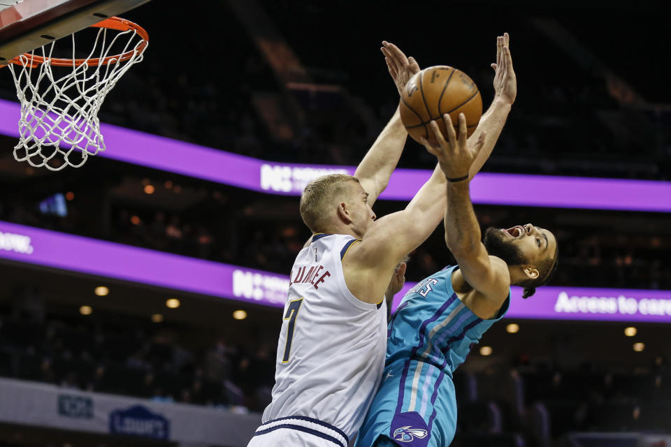 Denver Nuggets forward Mason Plumlee, left, fouls Charlotte Hornets forward Caleb Martin during the first half of an NBA basketball game in Charlotte, N.C., Thursday, March 5, 2020. (AP Photo/Nell Redmond)