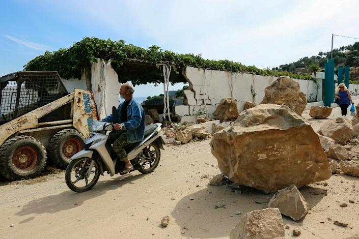 A man on motorcycle passes rubble in a street at the village Plomari, on the Greek island of Lesbos, on June 12, 2017 (AFP Photo/-)