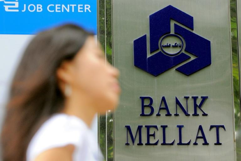 """Iran has claimed a """"victory"""" after one of its banks received compensation from British authorities over """"illegal"""" sanctions; in a file picture taken on September 8, 2010 a woman walks past a signboard of Bank Mellat, an Iranian state-run commercial bank, outside its Seoul branch"""
